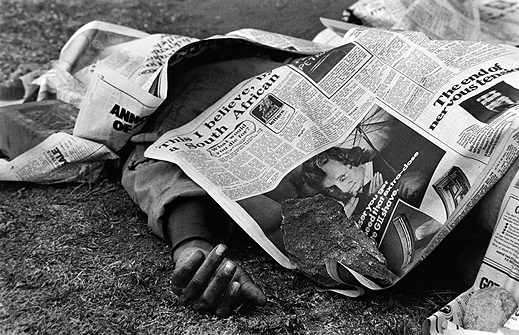 Peter Magubane, Dead bodies covered by newspaper filled the streets of Soweto during the 1976 riots, June 1976. Courtesy the artist.